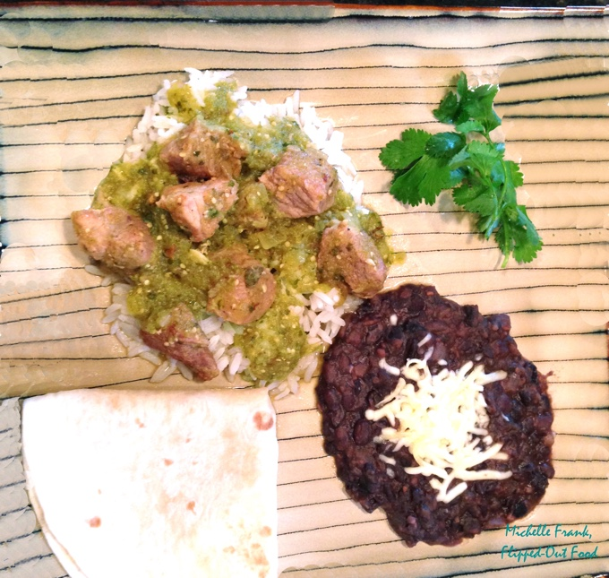 pork salsa verde on a striped plate, served with a side of black beans and a flour tortilla.