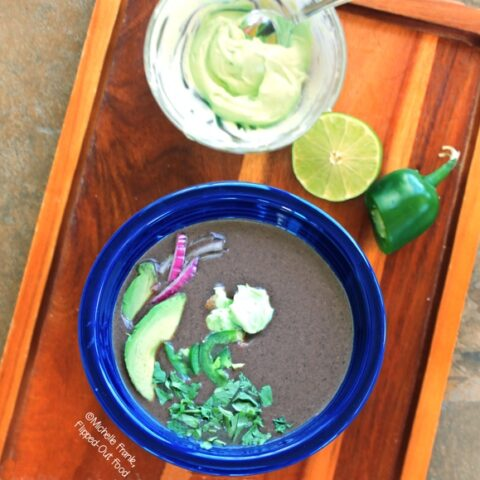 Slow-Cooker Black Bean Soup, in a blue bowl with avocado, cilantro, jalapenos, red onion, and avocado crema with lime and jalapeno in the background. #blackbeansoup #mexicanfood #slowcooker #crockpot #soup @FlippedOutFood