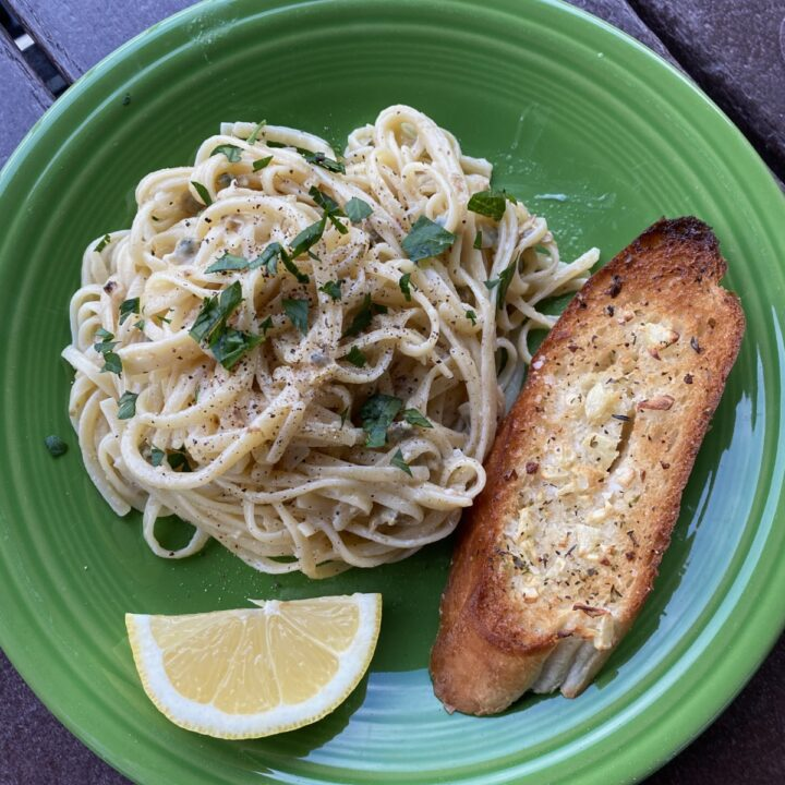 Pantry Linguine with Clam Sauce garnished with parsley, on a green plate with a toasted slice of garlic bread and a lemon wedge.