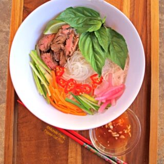 Bun Bo Xao: Vietnamese Lemongrass Beef Noodle Bowls: loaded bowl with chopsticks and nuoc cham. #vietnamesefood #bun #bunboxao #steak #lemongrass #ricenoodles @FlippedOutFood