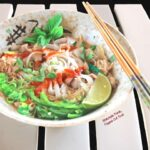 Slow-cooker Rotisserie Chicken Pho Ga, side view of a bowl loaded up with herbs, jalapenos, scallions, and sriracha. #vietnamesefood #phoga #pho #phonoodlesoup #vietnamesechickennoodlesoup @FlippedOutFood