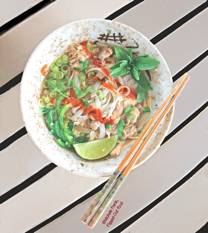 Slow-cooker Rotisserie Chicken Pho Ga, top view of a bowl loaded up with herbs, jalapenos, scallions, and sriracha. #vietnamesefood #phoga #pho #phonoodlesoup #vietnamesechickennoodlesoup @FlippedOutFood