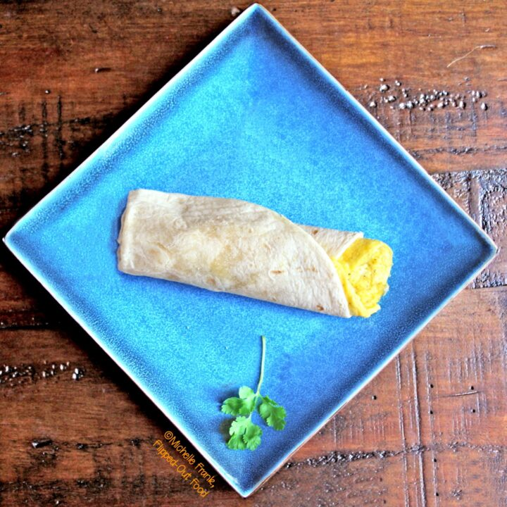 Green Chile Frittata Wraps: top view of a wrap set onto a square, blue plate with a sprig of cilantro.