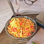 Dorm-Room Microwave Creamy Queso Spaghetti: close-up of a heaping serving amid piles of notes and geeky stuff.