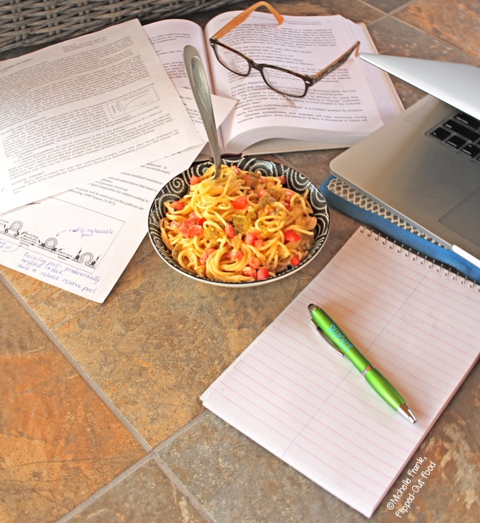 Dorm-Room Microwave Creamy Queso Spaghetti: a heaping serving amid piles of notes and geeky stuff.