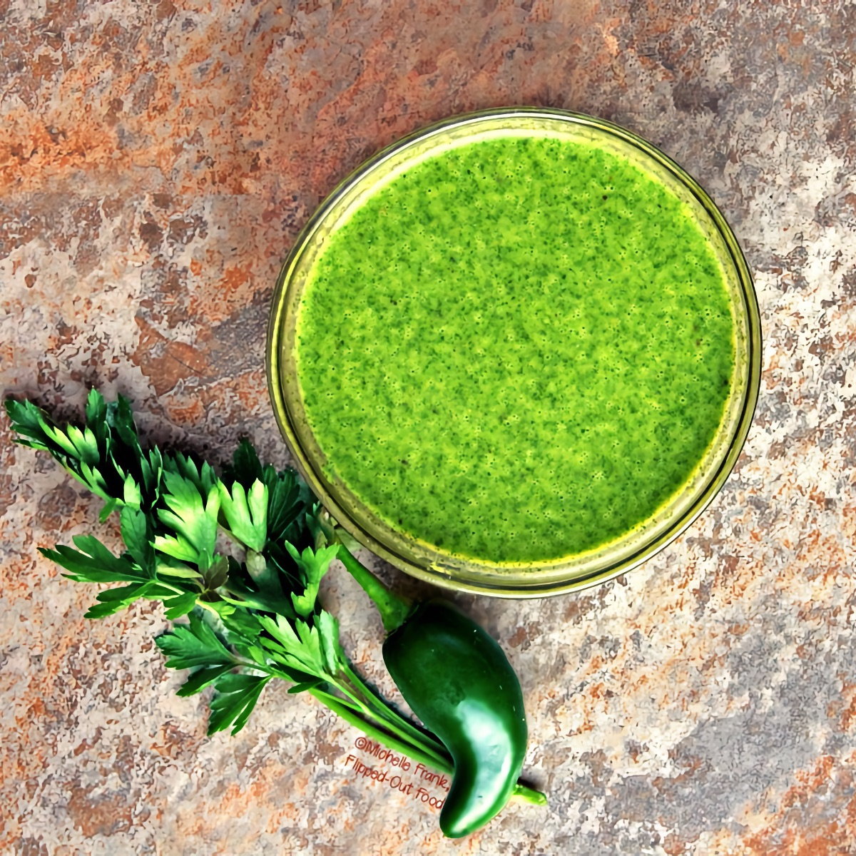 An overhead view of spicy chimichurri sauce, blended smooth and served in a ramekin. A jalapeño pepper and a sprig of parsley sit nearby.