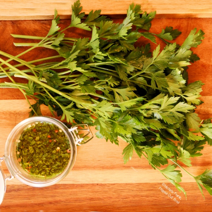 A jar of chimichurri sauce next to a bunch of parsley.