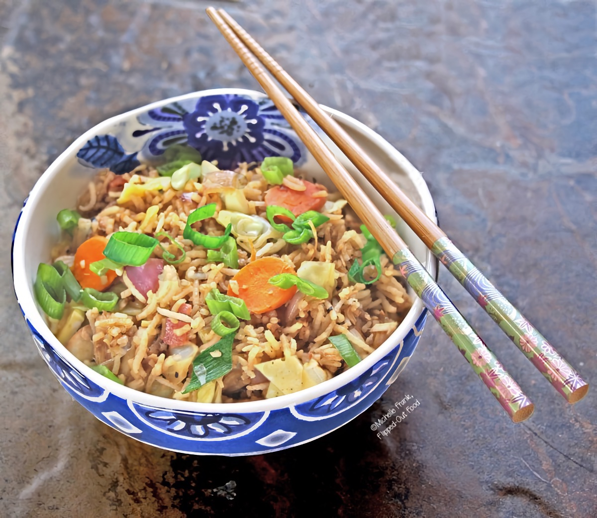 Leftover Vegetable Fried Rice in a blue and white ceramic bowl with a pair of chopsticks laying on top.