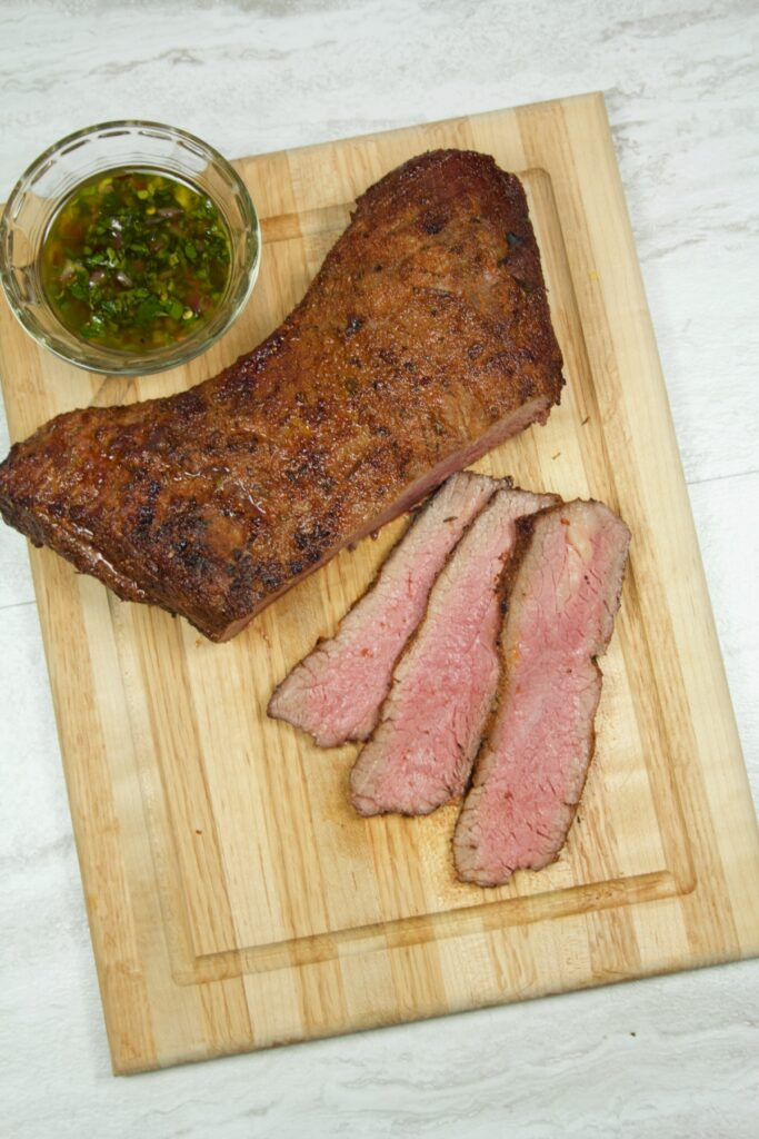 Overhead view of a tri-tip roast cut into thin steaks, with a ramekin of chimichurri sauce sitting nearby.
