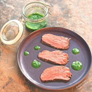 A side view of three slices of Grilled Tri-Tip Steak on a gray plate decorated with Chimichurri Sauce, sitting next to a jar of fresh chimichurri.