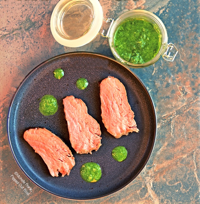 Grilled Tri-Tip Steak (overhead shot) with Chimichurri Sauce is a delicious pairing that is typical of Argentina and Brazil. The steak is flavorful and juicy—and perfectly accented by the tangy, fresh chimichurri sauce. #tritip #tritipsteak #chimichurrisauce #argentinianfood #grilledmeat #flippedoutfood #cookoutfood #brazilianfood #parillada #healthyfood via @FlippedOutFood