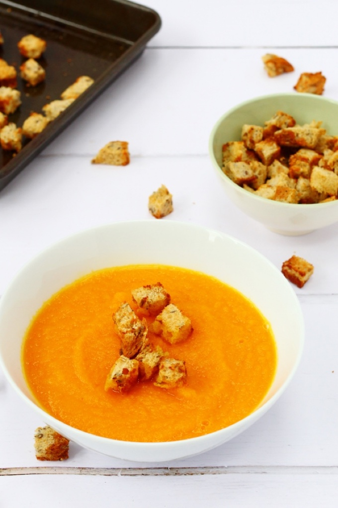 4 main dishes under 45: 1. A bowl of vibrant carrot and ginger soup with Marmite croutons. A few of the croutons are scattered on the table and a bowl of croutons sits in the background.