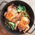 One-Pot Cornish Game Hens with Mushroom-Barley Pilaf: two hens, brown and crispy from roasting, arranged in a Staub Perfect Pan with sage sprigs atop the finished mushroom-barley pilaf.