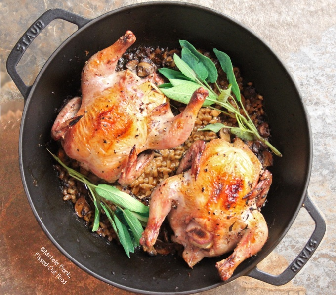 Easy One-Pot Meal Recipes: One-Pot Cornish Game Hens with Mushroom-Barley Pilaf: two hens, brown and crispy from roasting, arranged in a Staub Perfect Pan with sage sprigs atop the finished mushroom-barley pilaf.