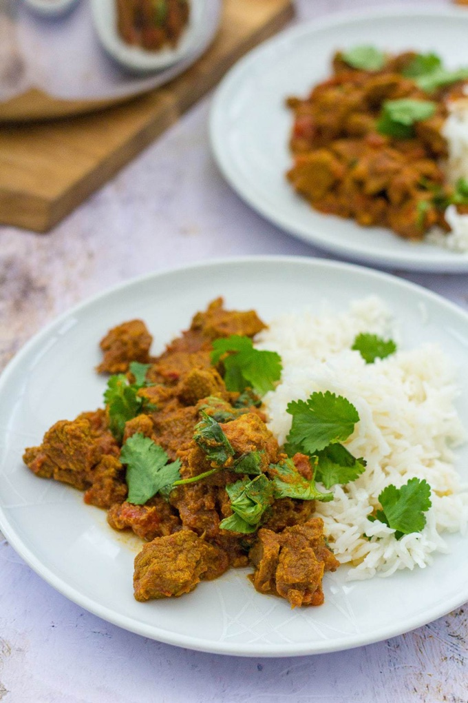 4 main dishes under 45: 2. a plate of Pressure Cooker Beef Curry, served with rice and sprinkled with cilantro. Another plate sits in the background next to a cutting board.