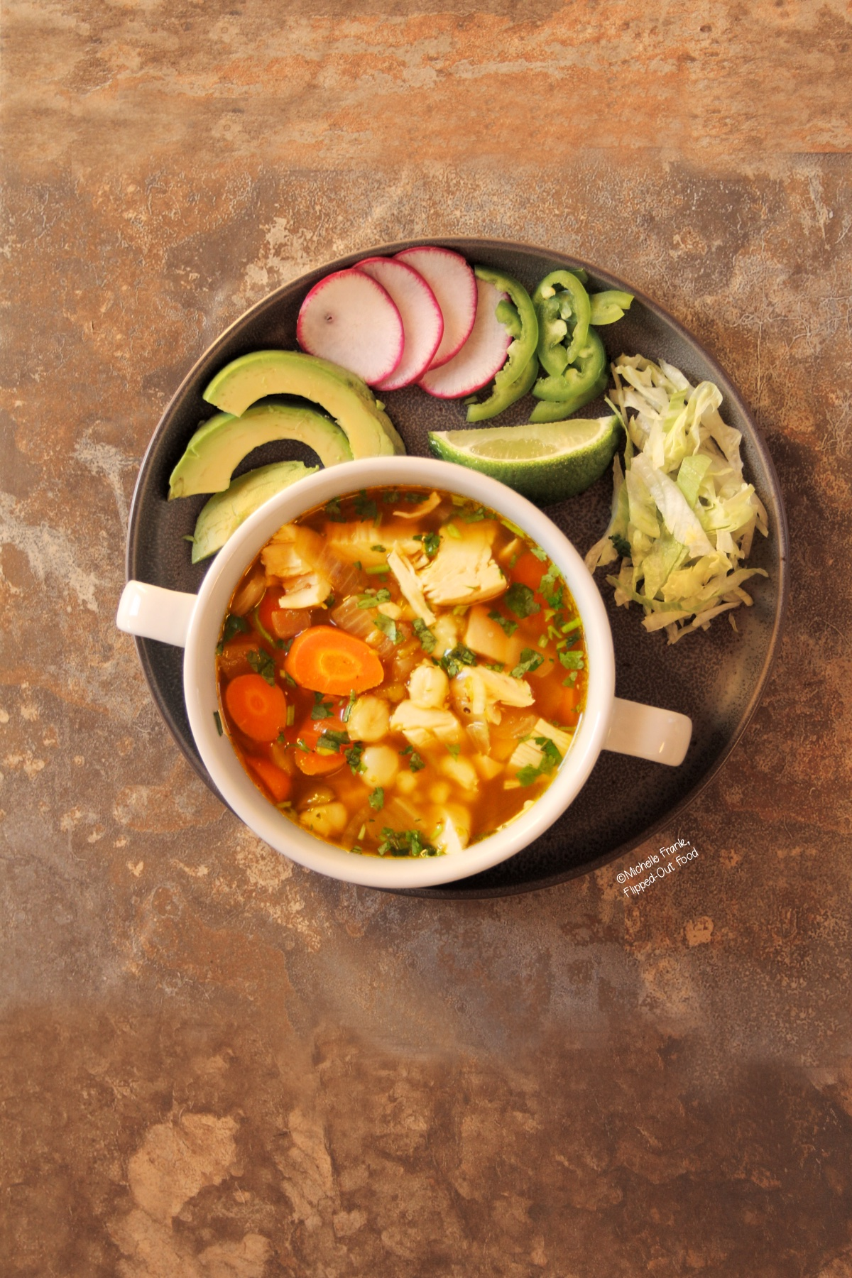 A serving of Green Chile Chicken Pozole in a white, 2-handled bowl. The bowl is set atop a round, grey plate with garnishes including sliced avocados, radishes, jalapenos and lettuce, along with a lime wedge.