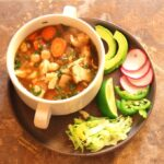 Green Chile Chicken Posole (Posole Verde de Pollo): a side view of a white, 2-handled bowl full of the posole sitting on a plate piled with garnishes, including avocado, thinly sliced radishes, jalapeno, lime, and shredded lettuce.