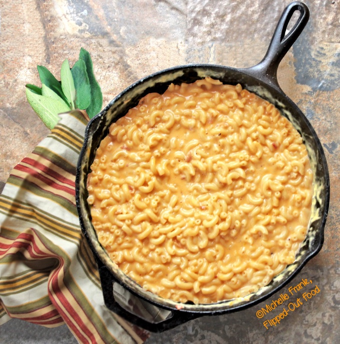 Creamy One-Pot Stovetop Macaroni and Cheese in a cast-iron skillet, next to a striped cloth and a bunch of sage. This macaroni and cheese is creamy and decadent, but without a roux or actual cream. Just loads of cheesy flavor!