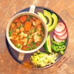 Green Chile Chicken Pozole (Pozole Verde de Pollo): a top view of a 2-handled bowl full of the pozole sitting on a plate piled with garnishes, including avocado, thinly sliced radishes, jalapeno, lime, and shredded lettuce.