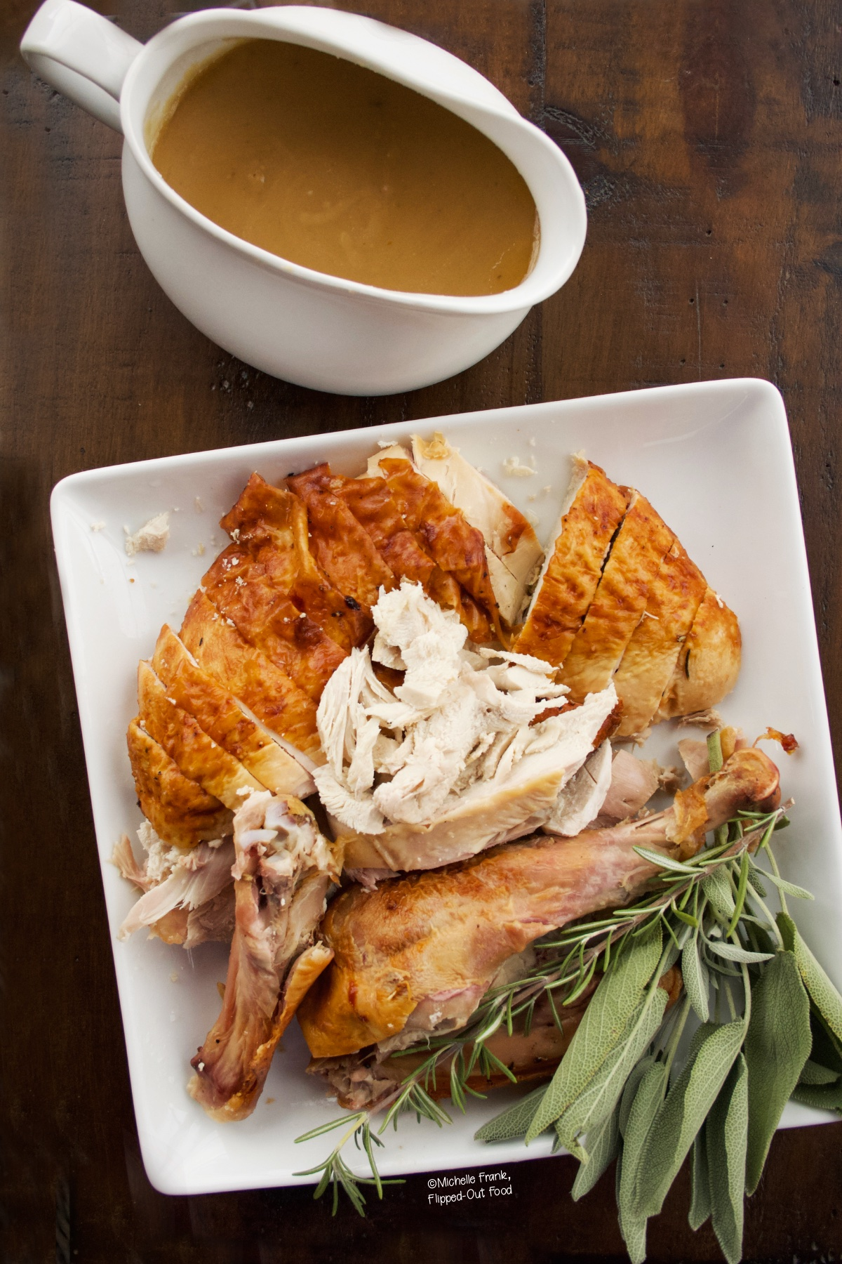 Easy Turkey Gravy in a white, porcelain gravy boat sitting next to a platter of sliced turkey garnished with sage.