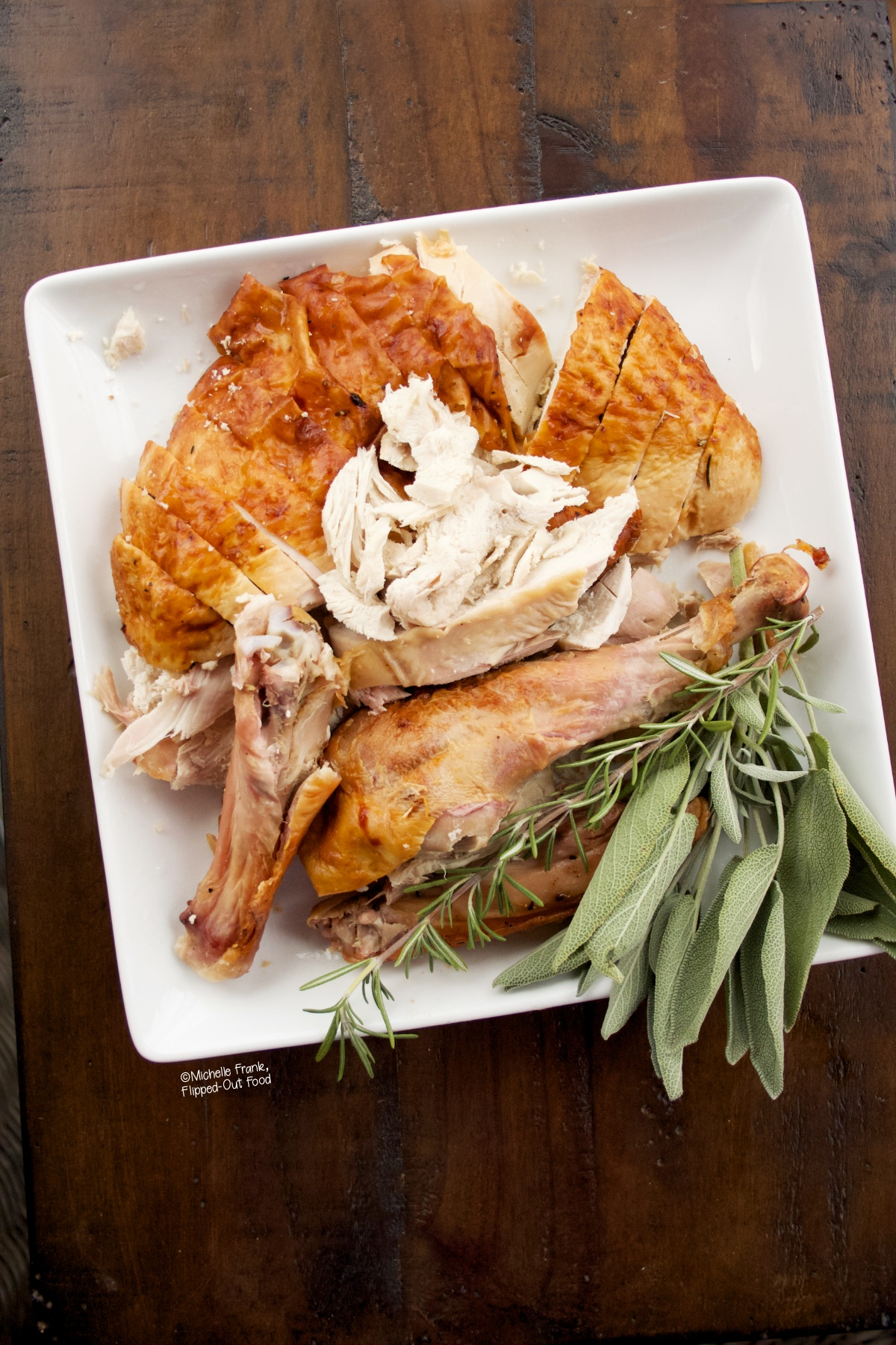 A white platter with sliced Ultimate Classic Roast Turkey, garnished with a bunch of fresh sage.