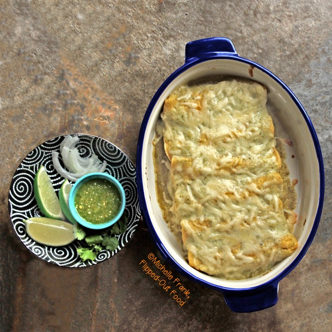 A blue casserole dish full of creamy green chile turkey enchiladas, next to a decorative plate of garnishes, including lime wedges, sliced white onions, cilantro, and a ramekin of salsa verde.