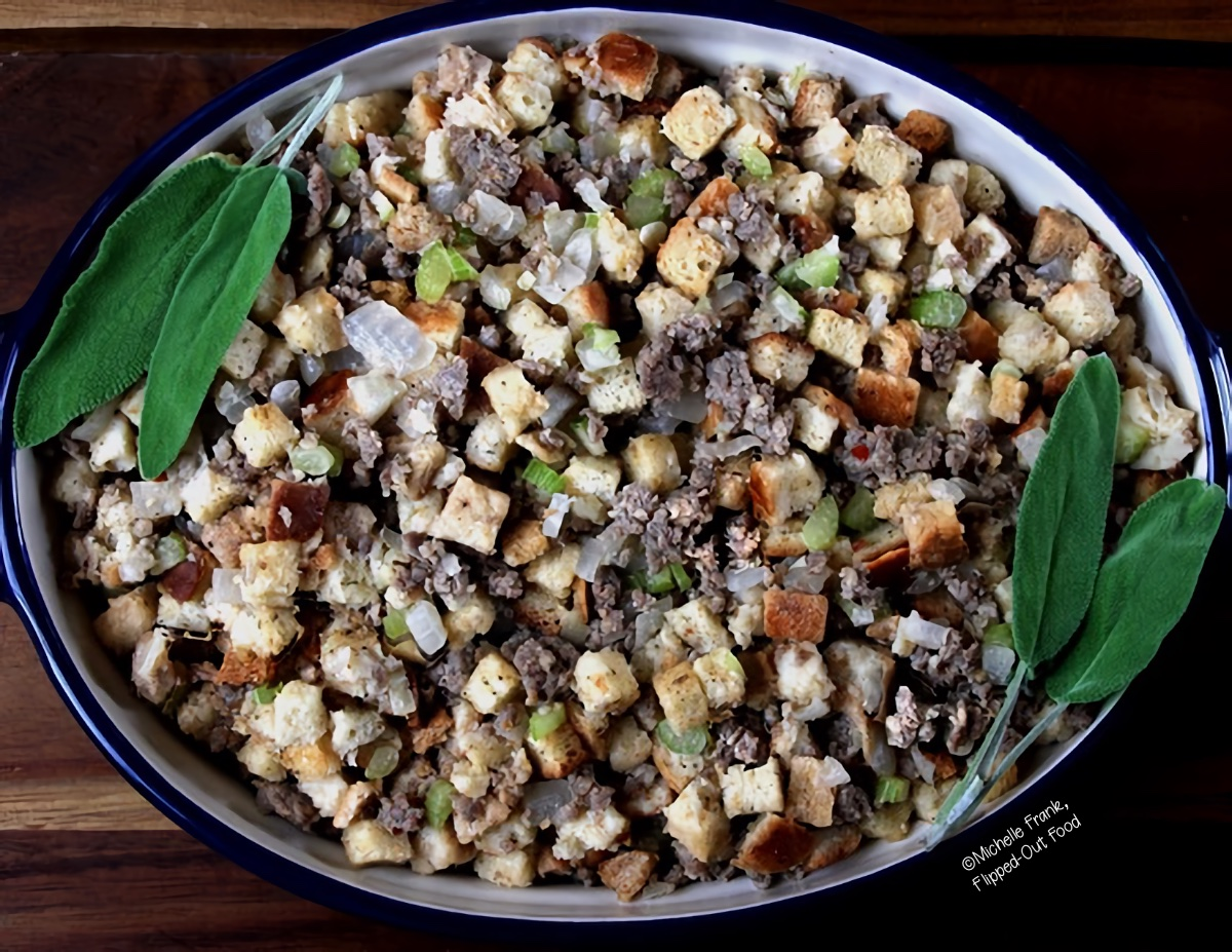 easy sausage stuffing in a ceramic baking dish, garnished with two sprigs of sage.