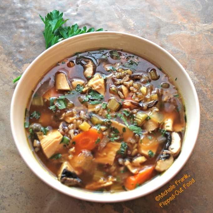 Side view of a ceramic bowl full of turkey wild rice soup. This angle especially shows the rich, concentrated broth, which is a dark, golden brown color.