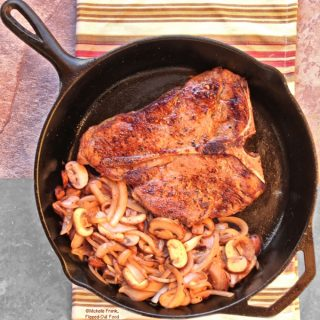 Steak Mushroom Onion Skillet: a porterhouse steak in a cast-iron skillet with caramelized mushrooms and onions. The skillet sits atop a colorful striped cloth.