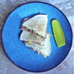 Three wedges of Cubano Quesadillas arranged on a bright blue plate next to a slice of dill pickle.