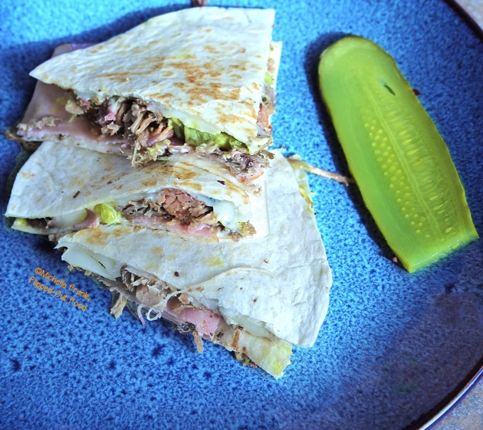 A close-up side view of three wedges of Cubano Quesadillas arranged on a bright blue plate next to a slice of dill pickle.