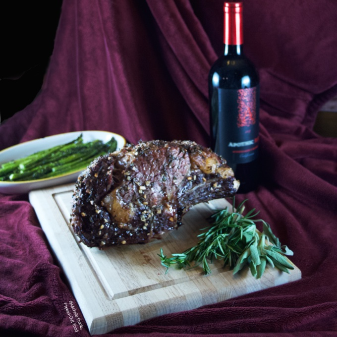 Date Night Prime Rib roast resting on a cutting board surrounded by herbs (rosemary and sage). In the background is a dish of roasted asparagus and a bottle of red wine.