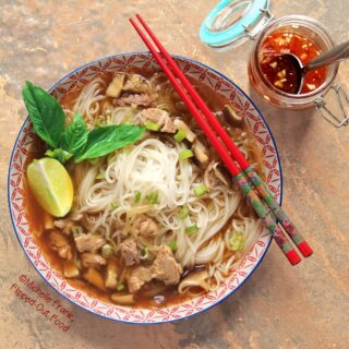 Overhead view of a bowl of slow-cooker duck pho in a shallow, patterned bowl with ornate, patterned pattern chopsticks sitting on top. The soup is garnished with Thai basil, sliced scallions, and a lime wedge. A small jar of nuoc cham sits to one side.