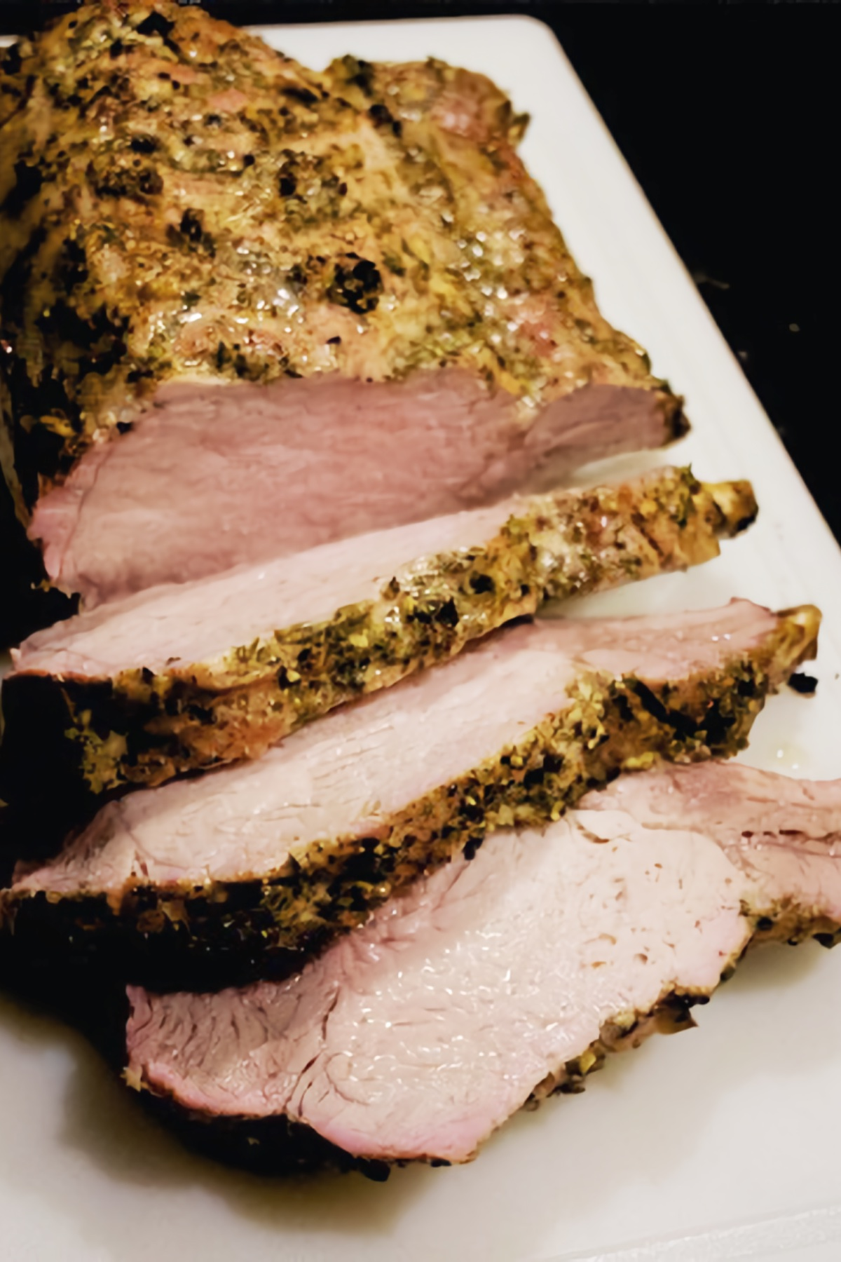 Herb-Roasted Rack of Pork sliced into huge chops on a cutting board.
