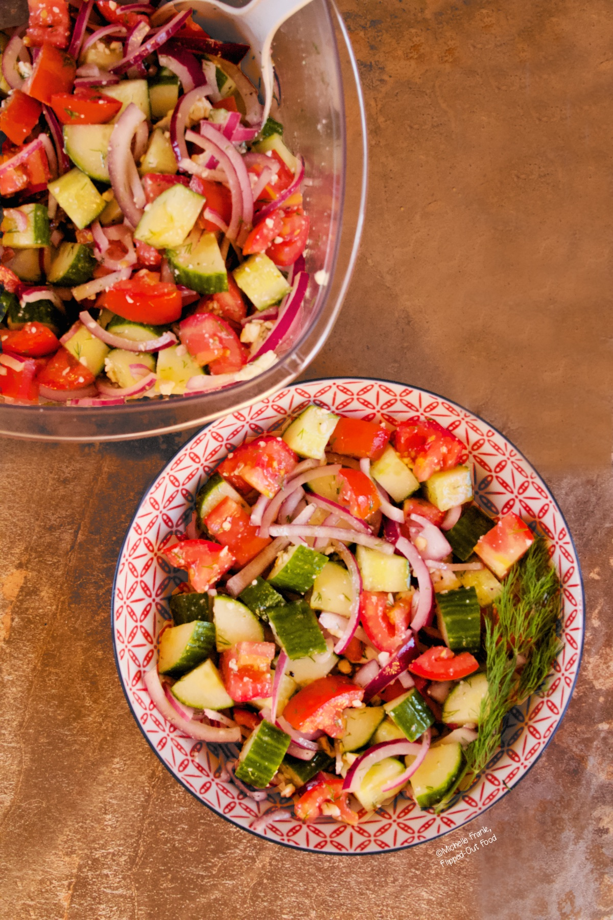 Cucumber-Tomato-Onion Salad in a red and white porcelain bowl. The salad is garnished with a sprig of dill, and sits in front of a storage container with more of the salad.