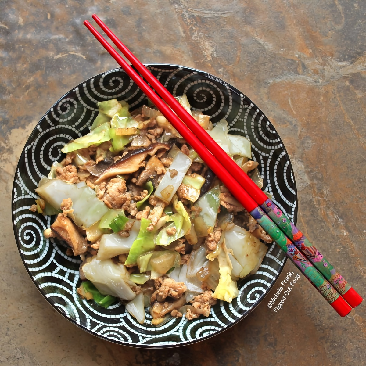 Overhead view of a serving of Inside-Out Egg Roll Bowl with a pair of colorful chopsticks sits atop the black and white oriental bowl.