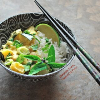 A side view of Easy Squash Curry in a decorative black bowl with white swirls. A pair of ornate chopsticks sits on top. The curry is served over basmati rice, with a sprig of Thai basil and a lime wedge.