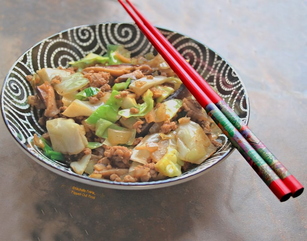 Inside-Out Egg Roll Bowls: a side view of a heaping serving in an ornate black bowl with white swirls. A pair of colorful chopsticks sits atop the bowl. The ends of the chopsticks are jumping out of the picture at you.