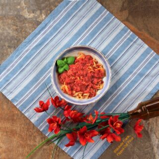 Top view of a bowl of chunky pantry marinara sauce in a light blue and white bowl sitting atop a blue and white striped cloth. The bowl sits next to a bunch of bright orange flowers. The spaghetti is garnished with a sprig of basil.