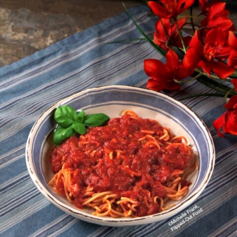 Side view of a serving of chunky pantry marinara sauce in a light blue and white bowl sitting atop a blue and white striped cloth. The bowl sits next to a bunch of bright orange flowers. The spaghetti is garnished with a sprig of basil.