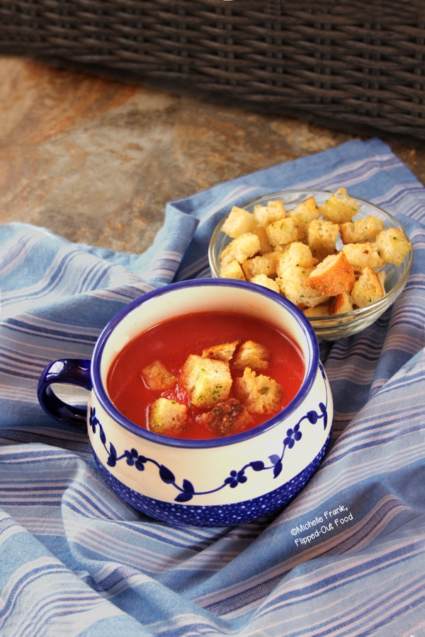Side view of Vegan Pantry Tomato Soup with Homemade Croutons in a decorative blue and white, single-handled bowl. The bowl sits on a blue and white-striped cloth. A bowl full of more croutons sits just behind.