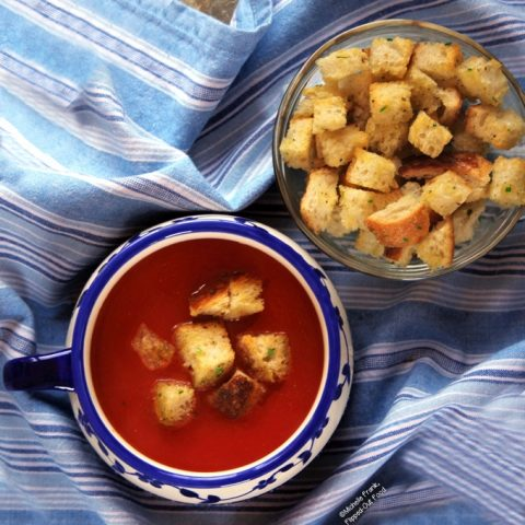 Top view of a serving of Vegan Pantry Tomato Soup with Homemade Croutons in a decorative blue and white, single-handled bowl. The bowl sits on a blue and white-striped cloth. A bowl full of more croutons sits just behind and to the right.