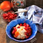 Side view of Maple-Orange-Strawberry Yogurt in a bright blue bowl. A piece of orange zest has been arranged to look like a flower. The bowl sits in front of a blue-and-white-striped cloth, a bowl with more strawberries, an orange, and a jug of maple syrup.