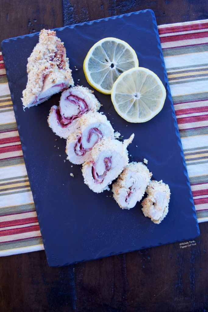 This Work-Ahead Chicken Rollatini recipe turns out perfectly cooked chicken pinwheels, like the ones picture here, sliced on a slate platter with lemon slices.