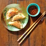 Top view of Pork-Shrimp Wontons with Soy-Ginger Dipping Sauce. Three wontons are arranged on a decorative, iridescent appetizer plate sprinkled with chopped chives. A blue ramekin with dipping sauce sits next to the plate and an ornate pair of chopsticks.