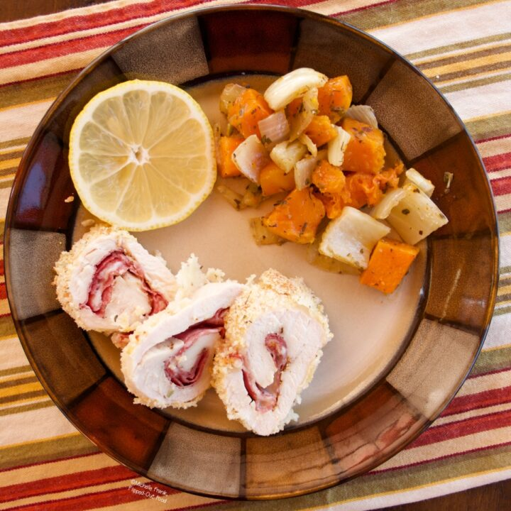 Work-Ahead Chicken Rollatini (Chicken Rollups) sliced on a ceramic plate with roasted vegetables and a slice of lemon.