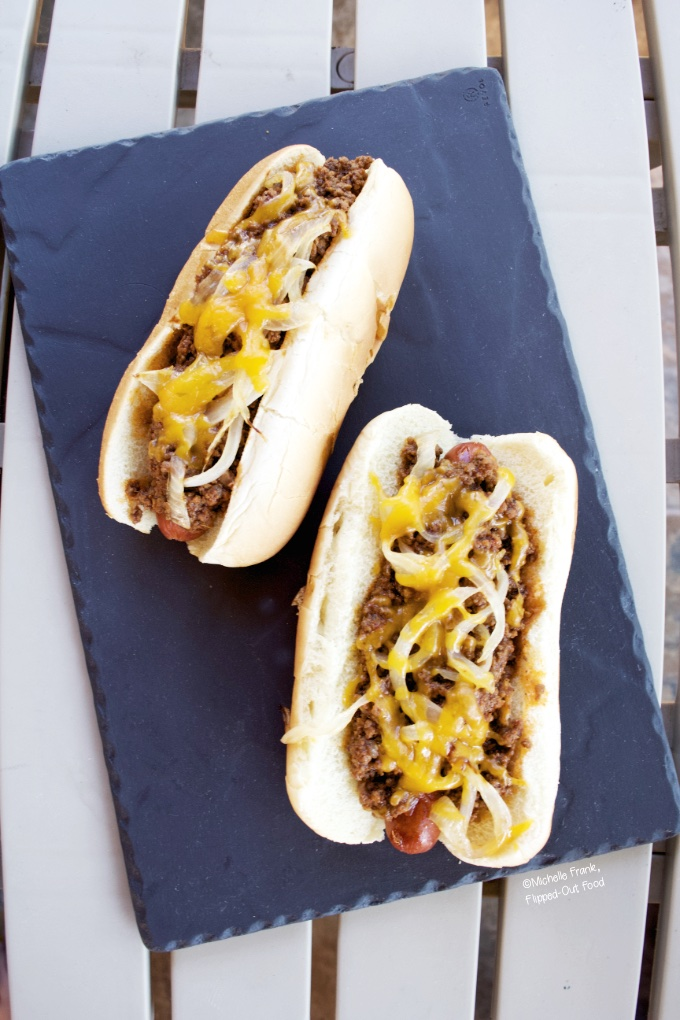 Two chili cheese dogs on a grey slate platter sitting atop a patio table.