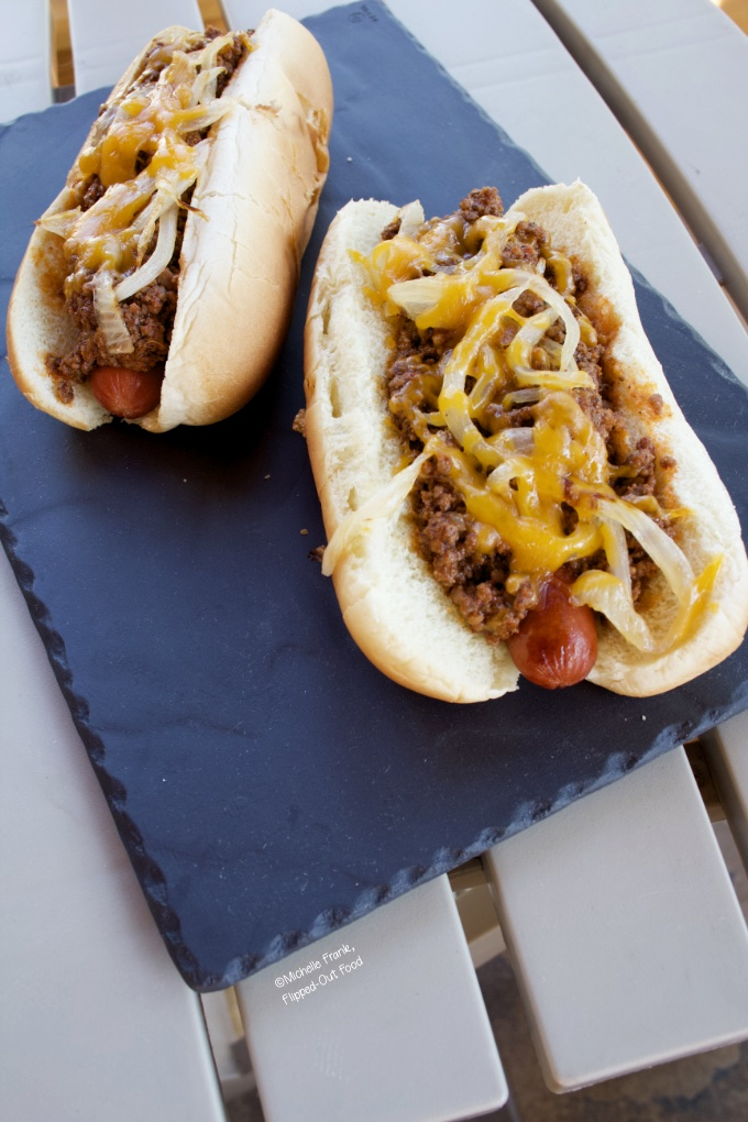 Side view of two chili cheese dogs on a grey slate platter sitting atop a patio table.