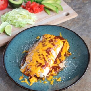 Lightened-Up Smothered Burritos: a burrito on a blue, ceramic plate. In the background sits a cutting board with various garnishes, including sliced avocados, sliced scallions, lime wedges, and chopped cilantro.