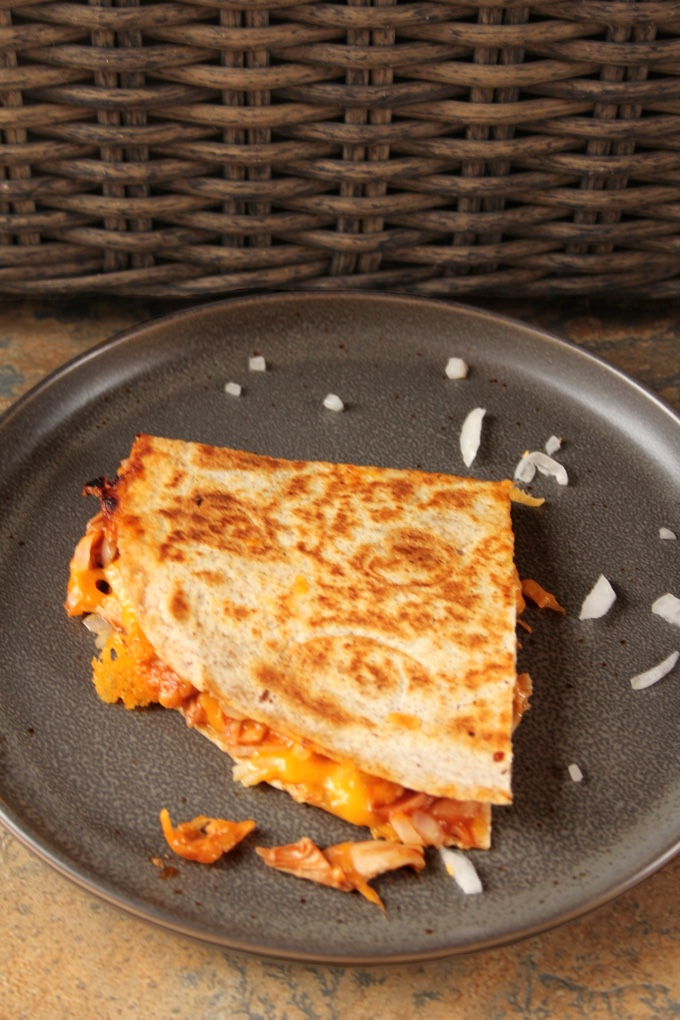 A slice of BBQ Chicken Quesadillas on a grey plate with a sprinkling of minced sweet onion.